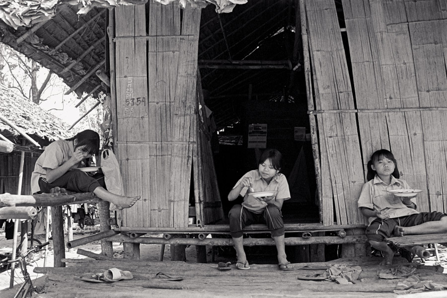 Rocky Mountain School: students eat lunch outside their dorms. Dorm styles vary widely at schools along the Thai-Burma border. Many are simple bamboo stilt-houses like these.