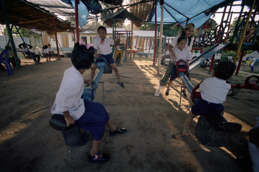 Agape School and Orphanage: children play with a continuing-ed student from Wide Horizons. Agape is one of the more well-supported migrant schools, where children wear uniforms similar to those of Thai students, and have  a beautiful playground featuring these seesaws, carousels, and jungle gyms.<br><br>**NOTE: Agape faced scandal in 2013 when its then-revered headmaster was accused of molestation and fled to Myanmar rather than face the police. The former headmaster spoke English well and solicited a great deal of support from foreigners, continuing to do so from unsuspecting friends after leaving Thailand.